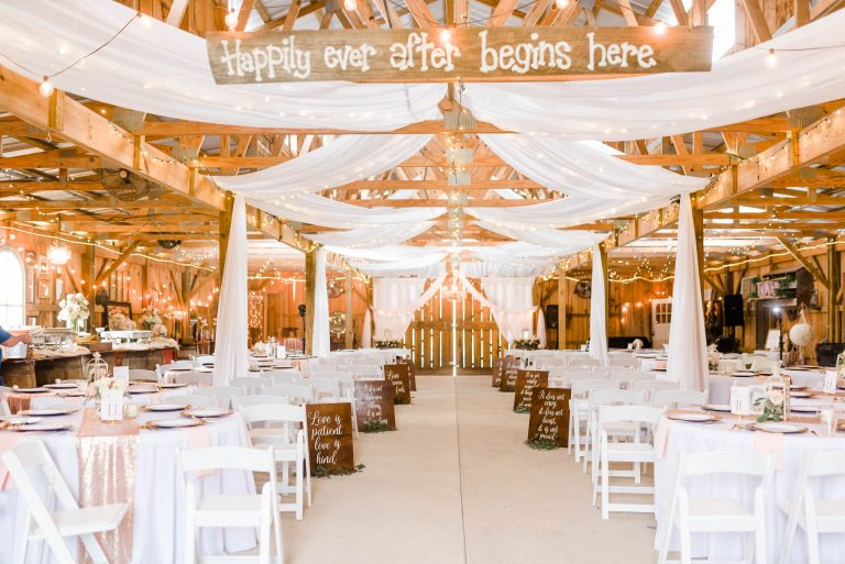 interior of barn for inside wedding ceremony with vintage wooden sign saying Happily ever after starts here.