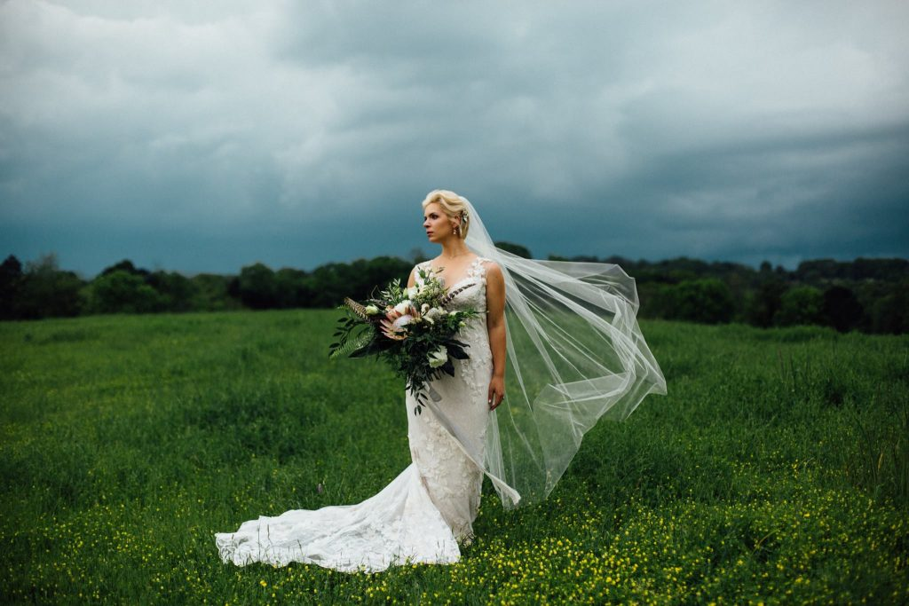 boho bride standing in a storm on a grassy hill in Tennessee