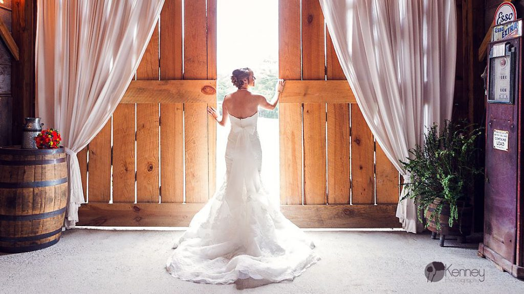 bride in white wedding dress standing in front of big barn doors at The barn at drewia hill