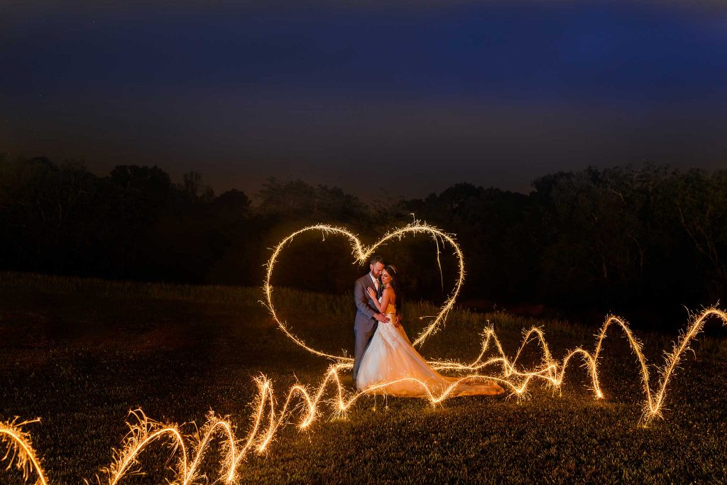 bride and groom with sparkler drawn heart and flames around them in the dark at The barn at drewia hill
