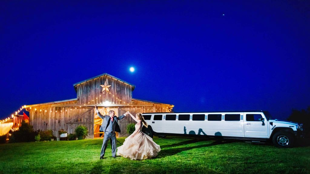 couple dancing at night in front of The barn at Drewia Hill with a white stretch Hummer Limo