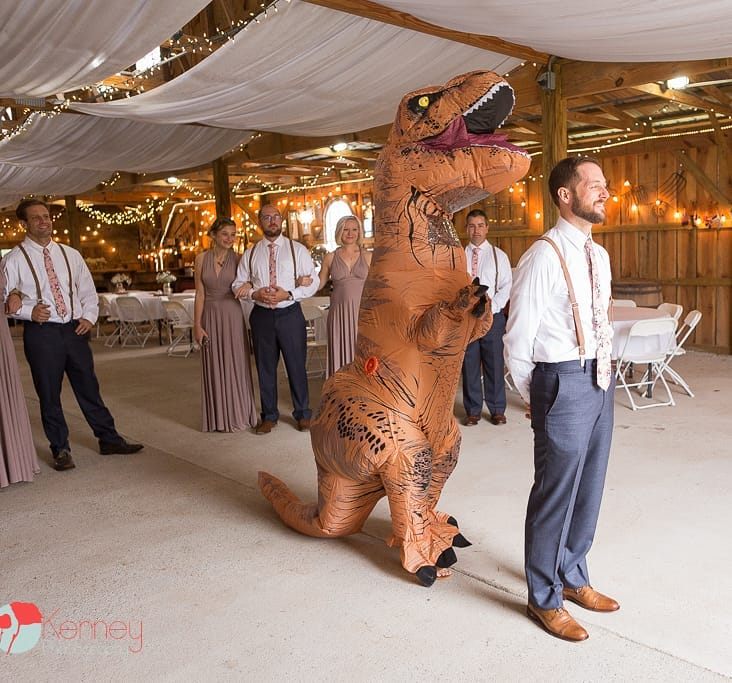 Bride in dinosaur costume walking up behind the groom at The Barn at Drewia hill wedding venue in Chattanooga